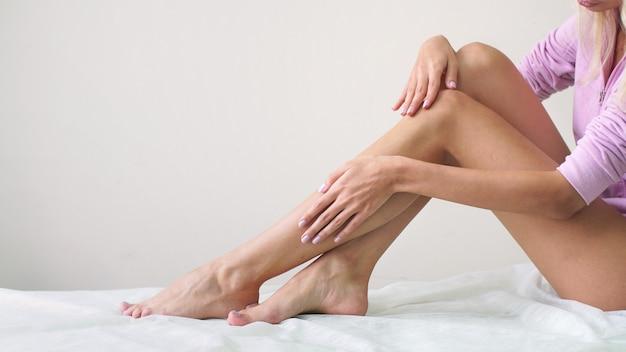 Молодая женщина с ухоженным телом после воска сидит с гладкими шелковистыми ножками