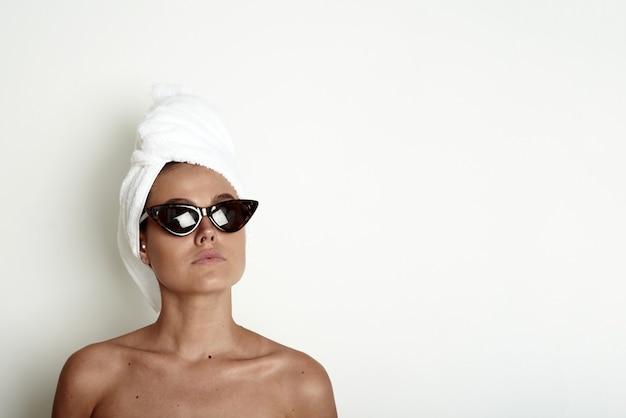 Молодая женщина с белым полотенцем на голове и в солнечных очках. утренняя концепция ухода за кожей, забавная модель. скопируйте пространство.