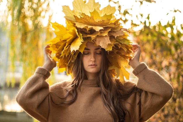 黄色い紅葉の花輪を持つ若い女性。屋外の肖像画。秋。
