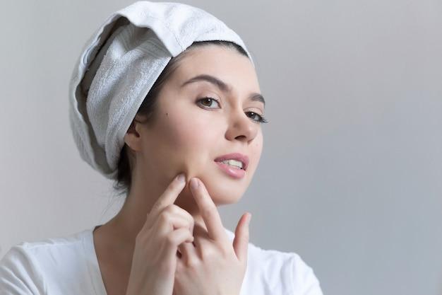 浴室のにきびを持つ若い女性