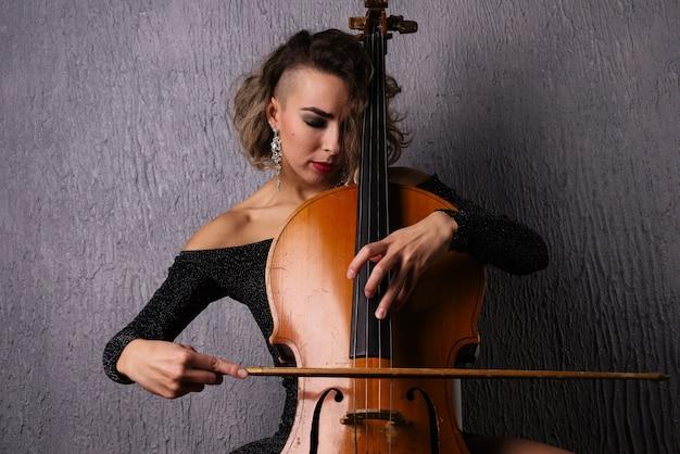 チェロを弾くニキビの若い女性