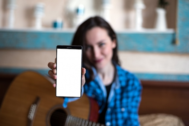 Young woman with acoustic guitar shows hand with smartphone.