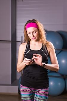 Молодая женщина с трекер активности и смартфон в тренажерном зале
