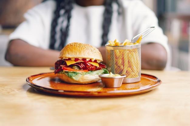 Молодая женщина с афро-волосами ест вкусный классический гамбургер с картофелем фри