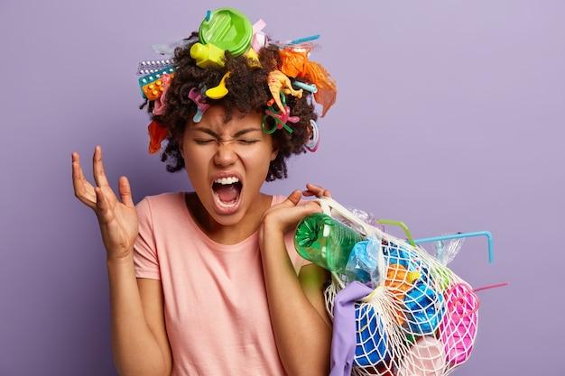 彼女の髪にアフロヘアカットとプラスチック廃棄物を持つ若い女性