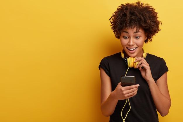 アフロの散髪と黄色のヘッドフォンを持つ若い女性