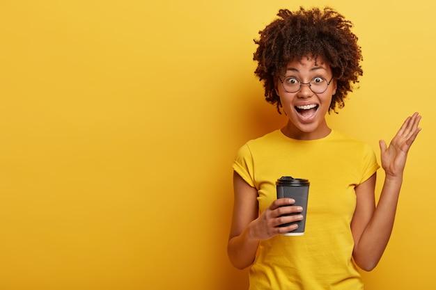 Молодая женщина с афро-стрижкой и желтой футболкой держит чашку кофе