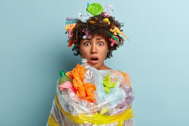 Young woman with afro haircut holding bag with plastic waste