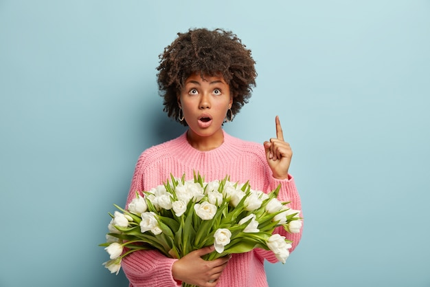 Молодая женщина с прической афро держит букет белых цветов