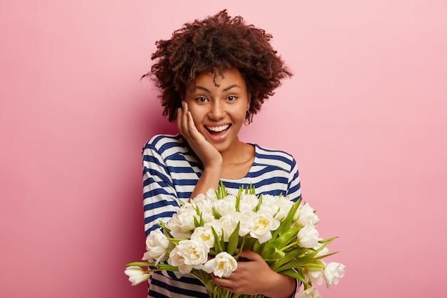 白い花の花束を保持しているアフロの散髪を持つ若い女性