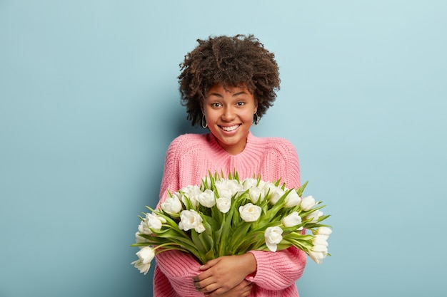 Young woman with afro haircut holding bouquet of white flowers