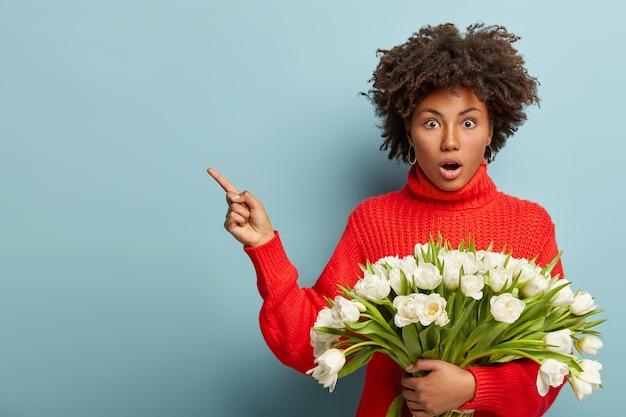 Giovane donna con taglio di capelli afro holding bouquet di fiori bianchi