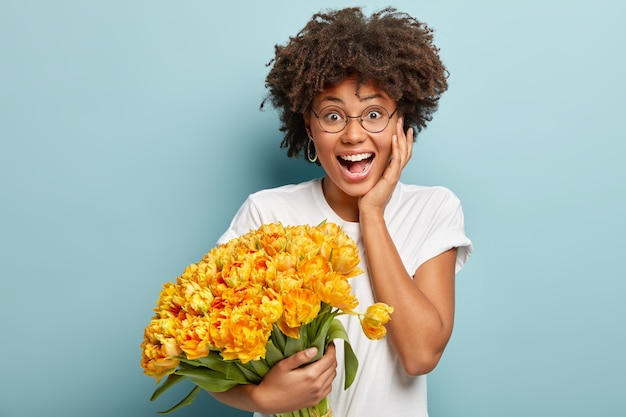 Young woman with afro haircut holding bouquet of yellow flowers