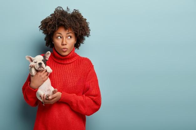 Молодая женщина с прической афро держит собачку