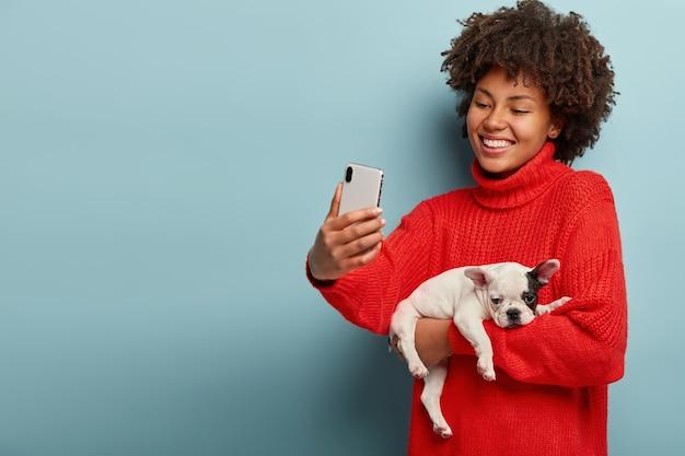小さな犬を保持しているアフロの散髪を持つ若い女性