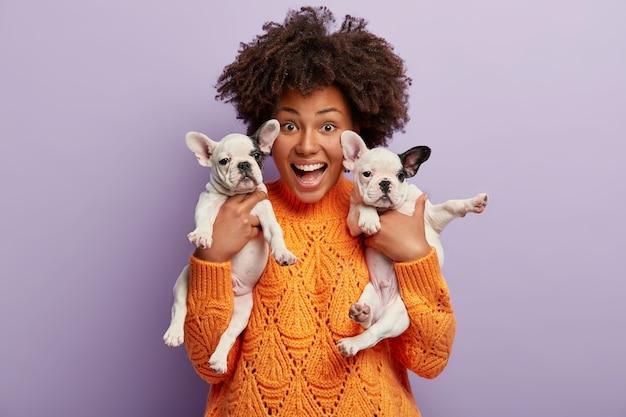 Giovane donna con taglio di capelli afro che tiene i cuccioli