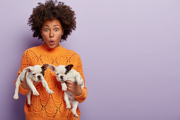 Young woman with afro haircut holding puppies
