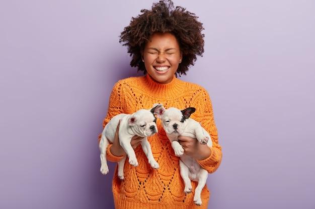 子犬を保持しているアフロの散髪を持つ若い女性