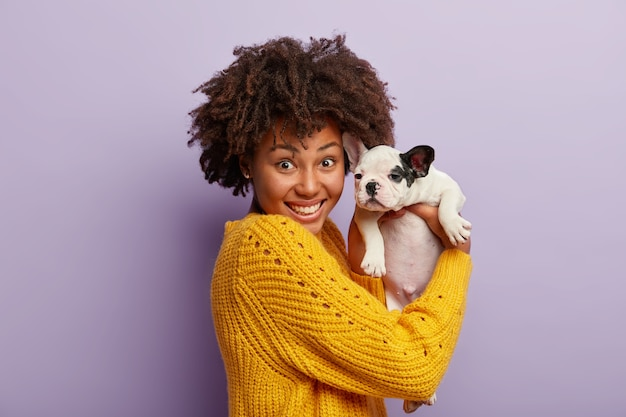 Young woman with afro haircut holding puppy