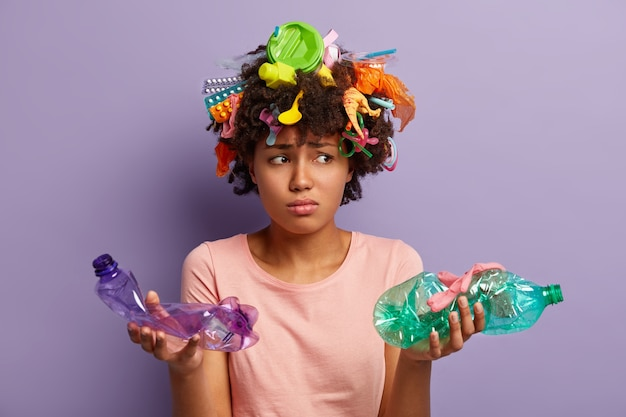 Giovane donna con taglio di capelli afro e rifiuti di plastica nei capelli
