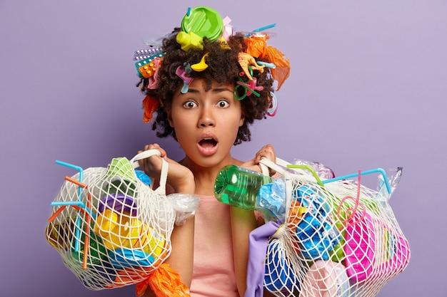 Giovane donna con taglio di capelli afro e rifiuti di plastica tra i capelli