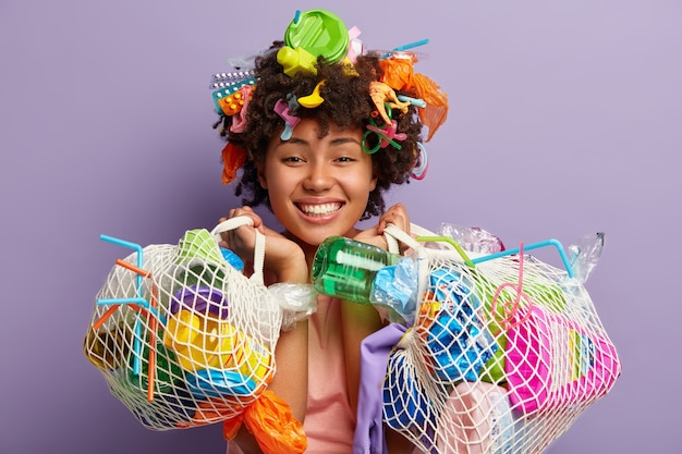 Young woman with afro haircut and plastic waste in her hair