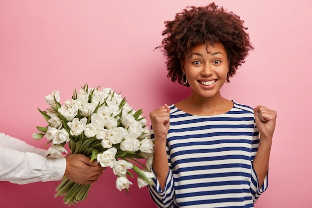 Молодая женщина с прической афро получает букет цветов