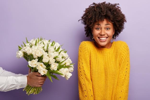 Молодая женщина с прической афро получает букет белых цветов