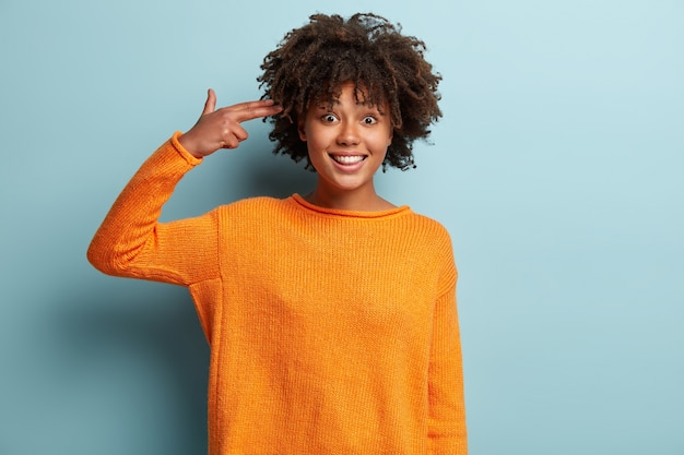 Молодая женщина со стрижкой афро в оранжевом джемпере