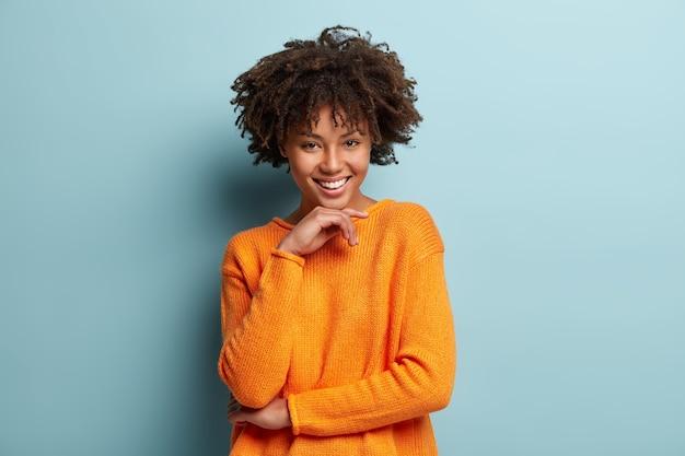 Giovane donna con taglio di capelli afro che indossa il ponticello arancione