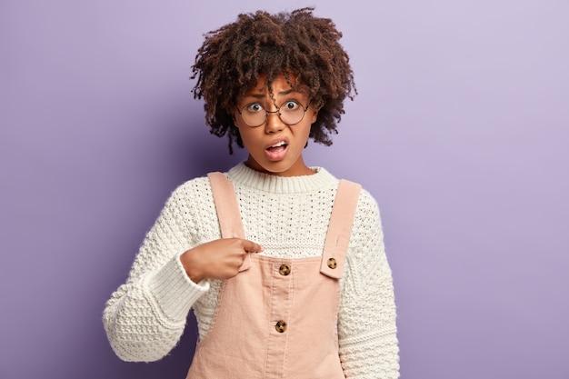 전체 분홍색과 스웨터를 입고 아프로 머리를 가진 젊은 여자