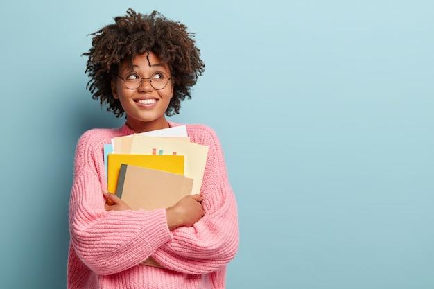 ピンクのセーターを着てアフロヘアカットの若い女性