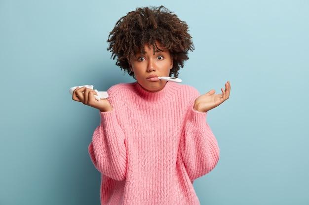 Giovane donna con taglio di capelli afro che indossa un maglione rosa
