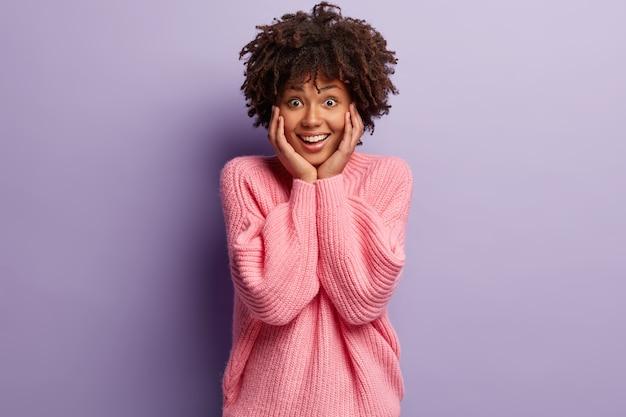 Молодая женщина с афро-стрижкой в розовом свитере