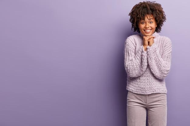 紫色のセーターを着てアフロの散髪を持つ若い女性