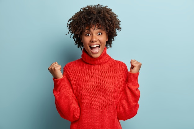Молодая женщина с афро-стрижкой в красном свитере