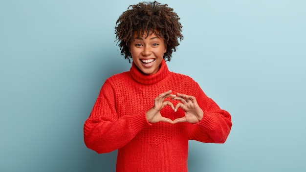 Young woman with afro haircut wearing red sweater