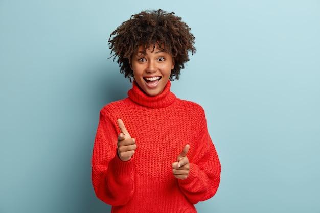 Giovane donna con taglio di capelli afro che indossa un maglione rosso