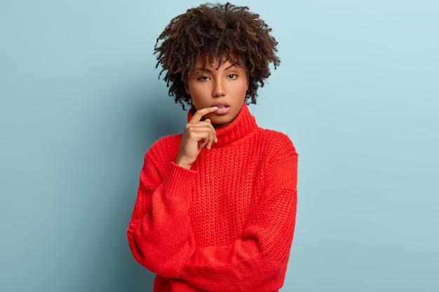 赤いセーターを着てアフロヘアカットの若い女性