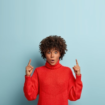 Giovane donna con taglio di capelli afro che indossa un maglione