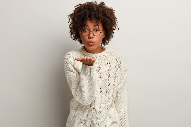 흰색 스웨터를 입고 아프로 머리를 가진 젊은 여자