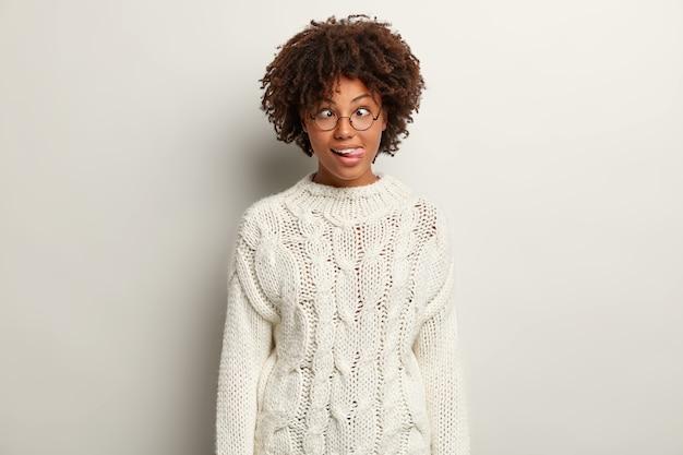 白いセーターを着てアフロヘアカットの若い女性