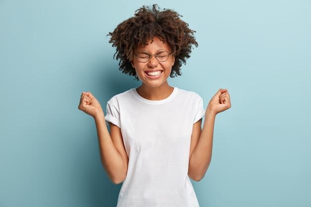 Giovane donna con taglio di capelli afro che indossa la maglietta bianca
