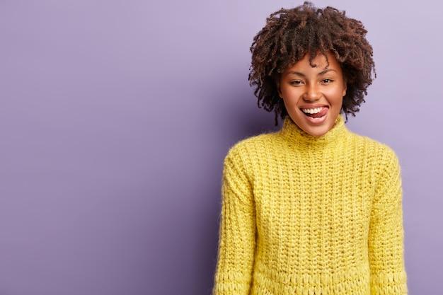 黄色のセーターを着てアフロヘアカットの若い女性