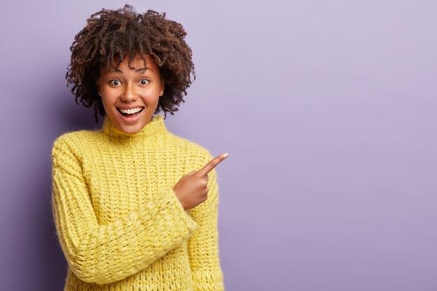 Giovane donna con taglio di capelli afro che indossa un maglione giallo