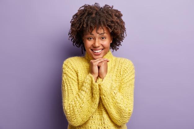 Молодая женщина с афро-стрижкой в желтом свитере