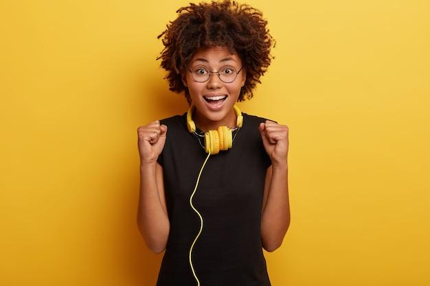 Giovane donna con taglio di capelli afro con cuffie gialle