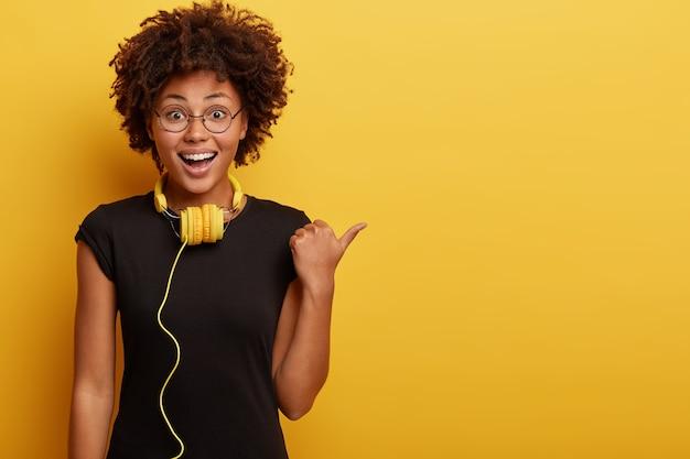 黄色のヘッドフォンでアフロヘアカットの若い女性