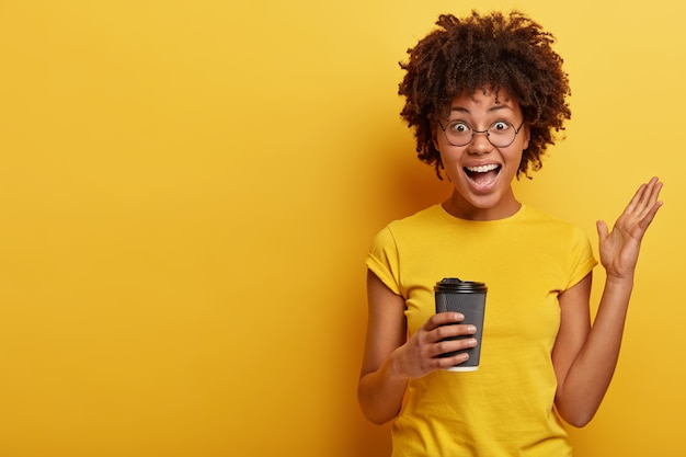 Young woman with afro haircut and yellow t-shirt holding cup of coffee