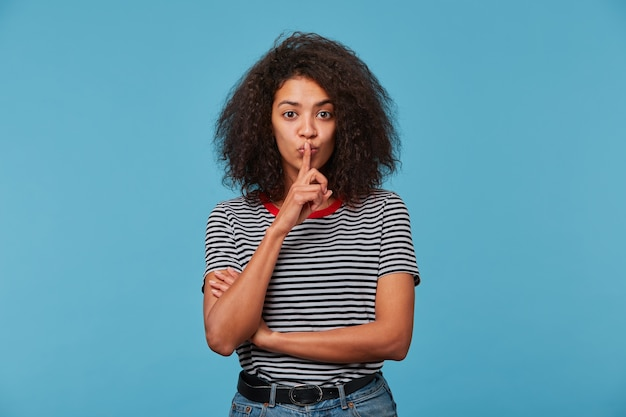 Giovane donna con l'acconciatura afro che indossa la maglietta spogliata sopra isolato